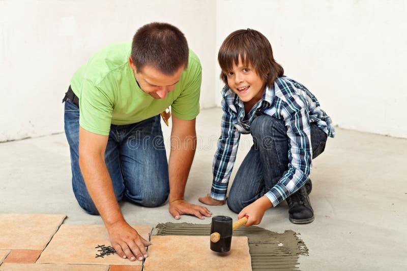 Αγόρι που βοηθά τον πατέρα του που τοποθετεί ένα κεραμικό κεραμίδι πατωμάτων στοκ εικόνα