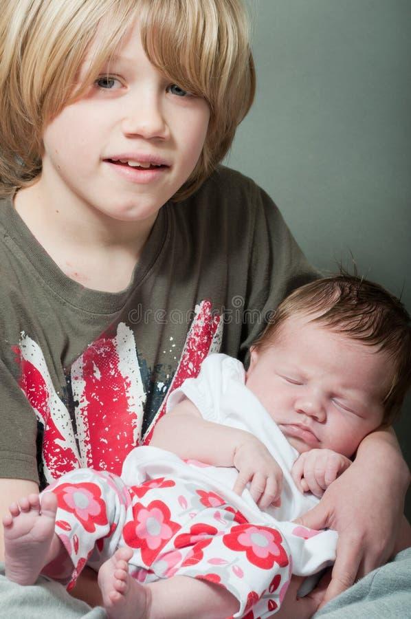 Αγόρι που κρατά έναν νέο - γεννημένο μωρό στοκ εικόνες με δικαίωμα ελεύθερης χρήσης