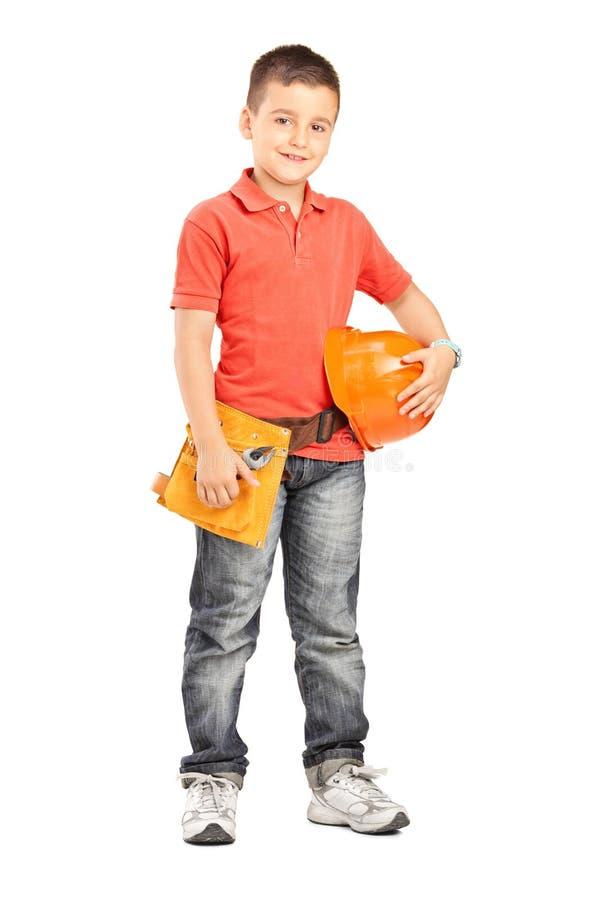 Αγόρι που κρατά ένα κράνος και που φορά μια ζώνη εργαλείων στοκ φωτογραφίες