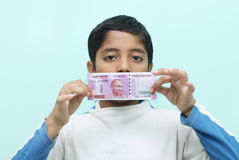 Αγόρι που κρατά τις νέες ινδικές πιστώσεις ρουπίων του 2000 στο χέρι του στοκ εικόνες με δικαίωμα ελεύθερης χρήσης