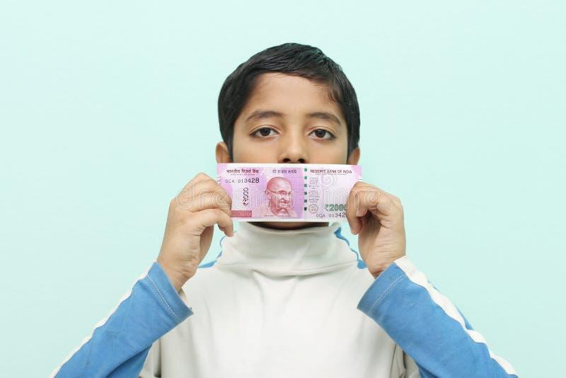 Αγόρι που κρατά τις νέες ινδικές πιστώσεις ρουπίων του 2000 στο χέρι του στοκ εικόνα