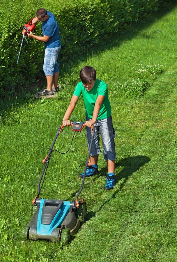 Αγόρι που κόβει το χορτοτάπητα ενώ ο πατέρας του τακτοποιεί το φράκτη στοκ εικόνα με δικαίωμα ελεύθερης χρήσης
