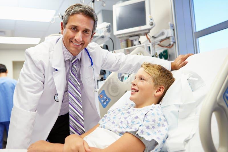Αγόρι που μιλά στον αρσενικό γιατρό στη εντατική στοκ εικόνα με δικαίωμα ελεύθερης χρήσης