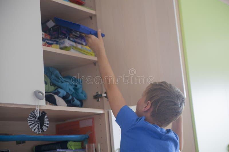 Αγόρι που οργανώνει την κρεβατοκάμαρά του στοκ φωτογραφία με δικαίωμα ελεύθερης χρήσης