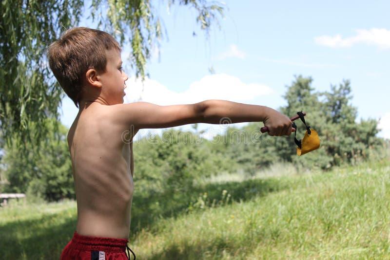 Αγόρι που παίρνει το στόχο από μια σφεντόνα προς στοκ φωτογραφία με δικαίωμα ελεύθερης χρήσης