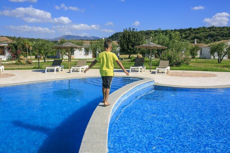 Αγόρι που περπατά πέρα από την πισίνα στοκ εικόνα