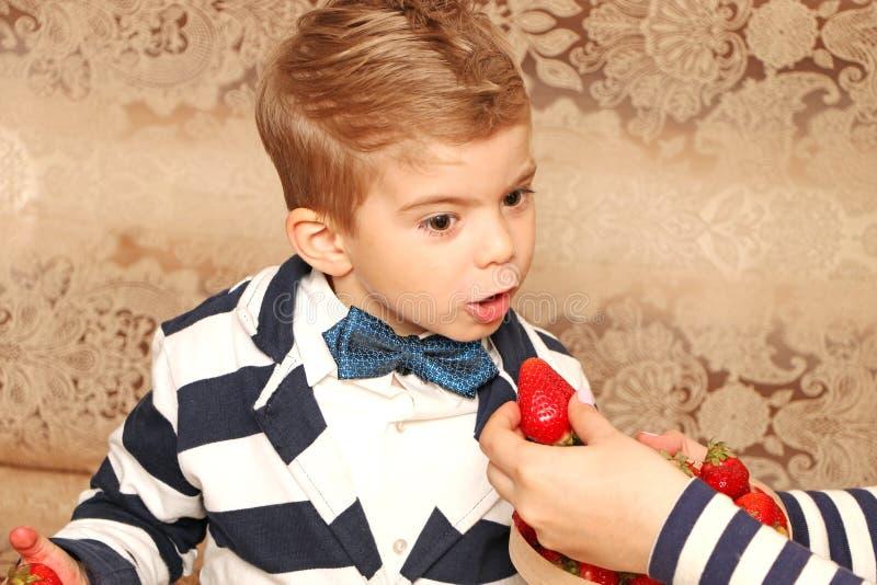 Αγόρι που που τρώει τις νόστιμες φράουλες στοκ φωτογραφία