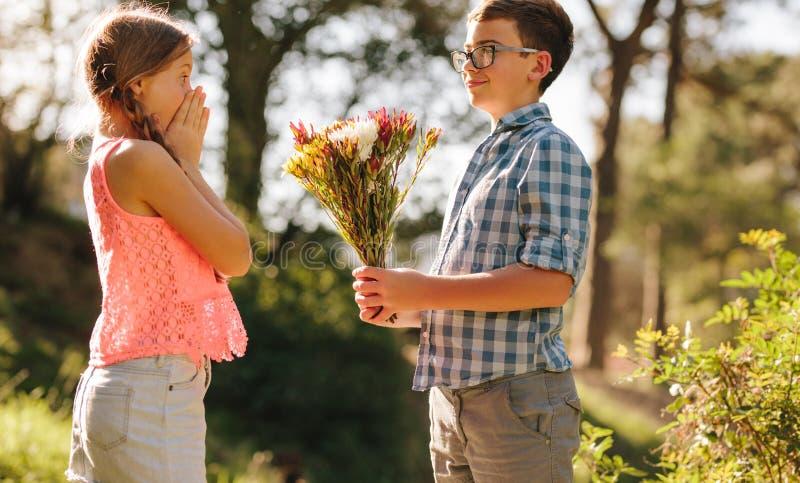 Αγόρι που προτείνει στη φίλη του με τα λουλούδια στοκ φωτογραφίες με δικαίωμα ελεύθερης χρήσης