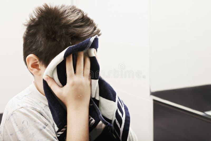 Αγόρι που σκουπίζει το πρόσωπό του με την πετσέτα στοκ εικόνες