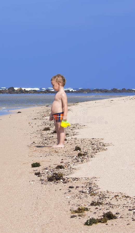 Αγόρι που στέκεται στην παραλία στοκ εικόνα με δικαίωμα ελεύθερης χρήσης