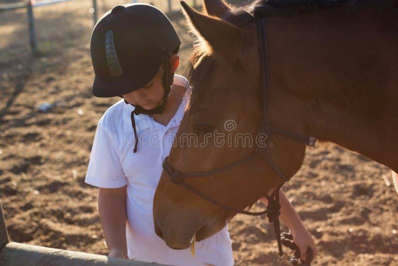 Αγόρι που ταΐζει το άλογο στο αγρόκτημα στοκ εικόνα με δικαίωμα ελεύθερης χρήσης