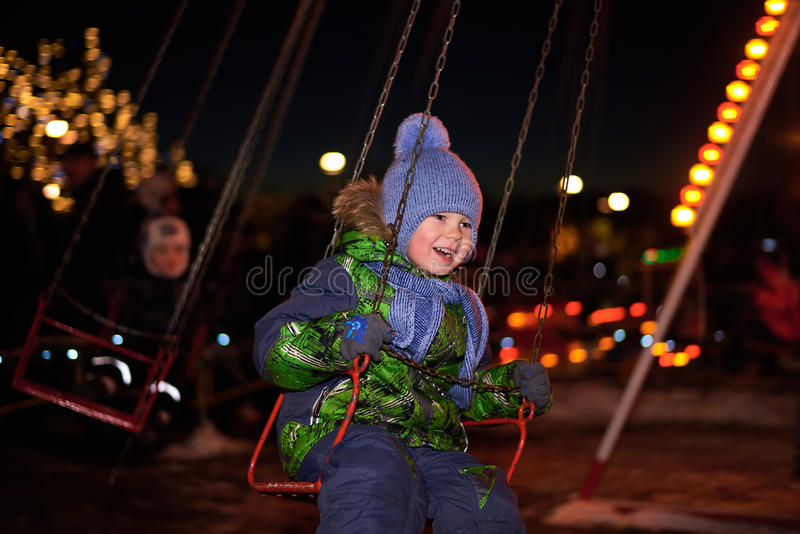 Αγόρι που ταλαντεύεται σε μια ταλάντευση στη νύχτα στοκ εικόνα με δικαίωμα ελεύθερης χρήσης