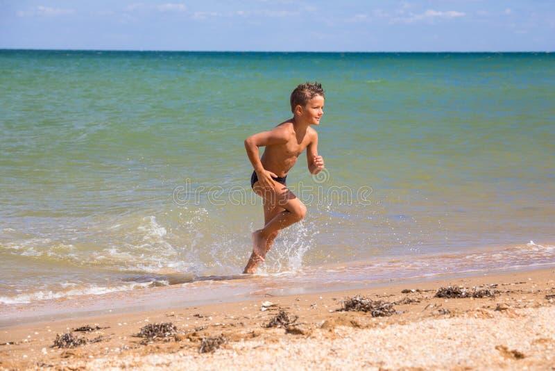 Αγόρι που τρέχει από τη θάλασσα στην παραλία στοκ εικόνες