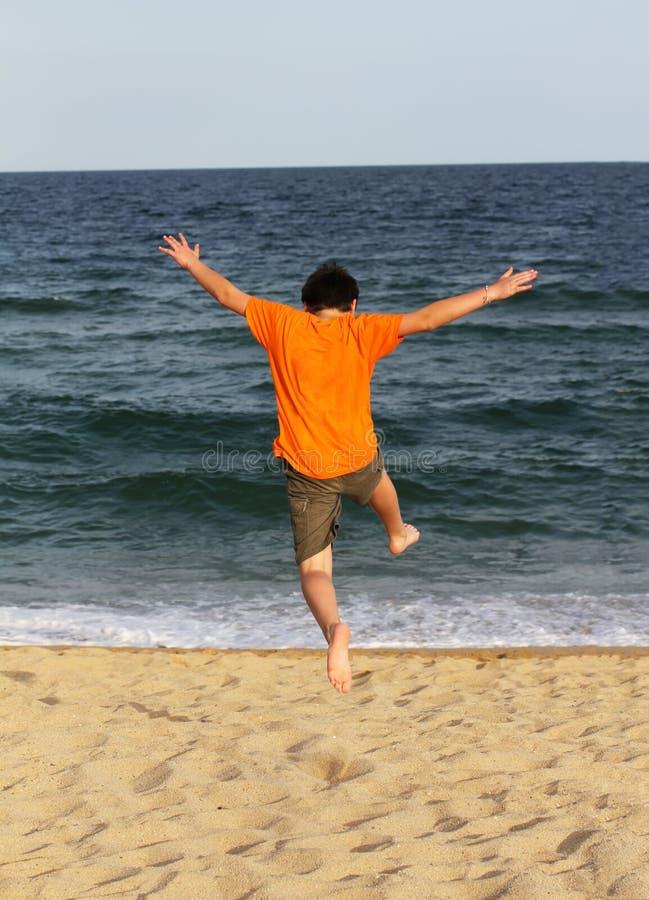 Αγόρι που τρέχει στη θάλασσα στοκ φωτογραφίες