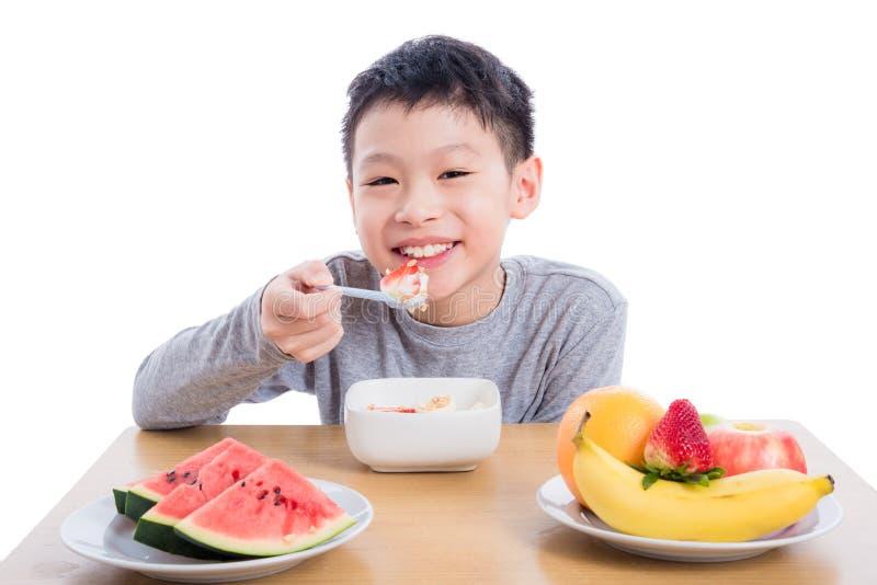 Αγόρι που τρώει τα δημητριακά με το γιαούρτι για το πρόγευμα πέρα από το λευκό στοκ εικόνες