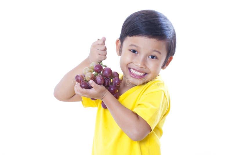 αγόρι που τρώει τα σταφύλια στοκ φωτογραφίες