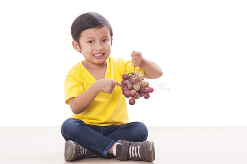 αγόρι που τρώει τα σταφύλια στοκ φωτογραφία