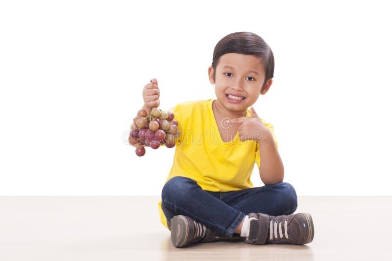 αγόρι που τρώει τα σταφύλια στοκ εικόνες