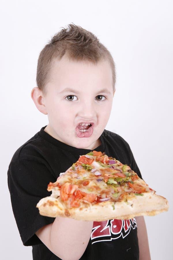 αγόρι που τρώει τη φέτα πιτσώ στοκ φωτογραφίες