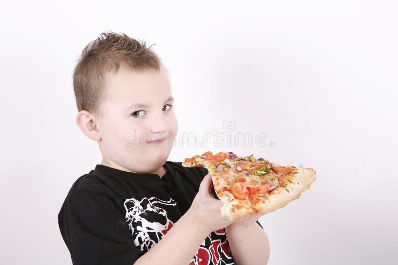 αγόρι που τρώει τη φέτα πιτσώ στοκ εικόνα