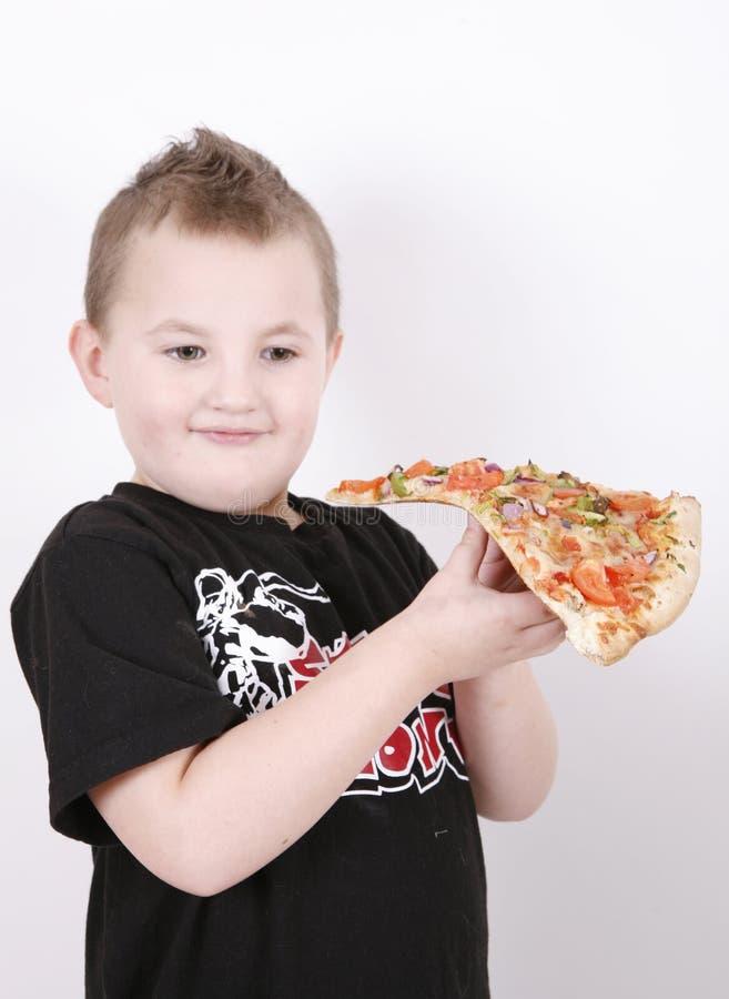 αγόρι που τρώει τη φέτα πιτσώ στοκ φωτογραφία με δικαίωμα ελεύθερης χρήσης