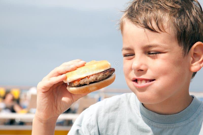 Αγόρι που τρώει το χάμπουργκερ στο σκάφος στοκ φωτογραφίες με δικαίωμα ελεύθερης χρήσης