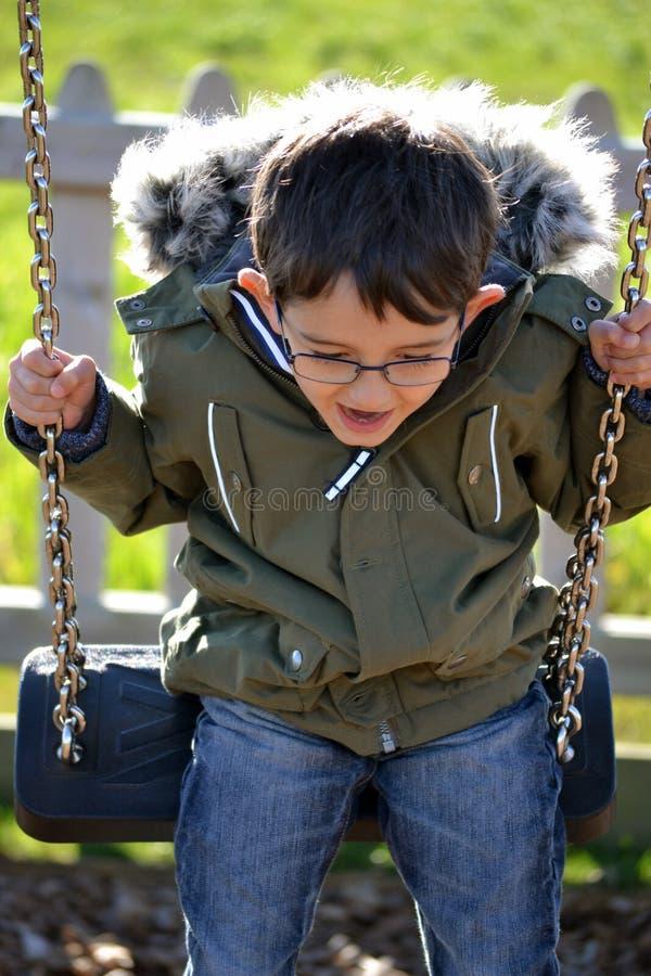 Αγόρι που φορά το παλτό στην ταλάντευση στοκ εικόνες