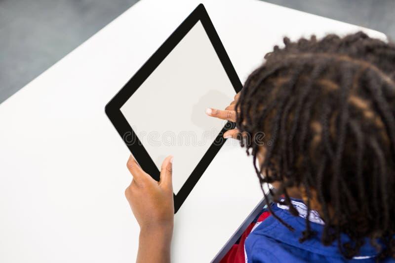 Αγόρι που χρησιμοποιεί την ψηφιακή ταμπλέτα στην τάξη στοκ εικόνες