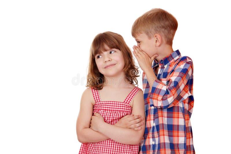 Αγόρι που ψιθυρίζει ένα μυστικό μικρό κορίτσι στοκ φωτογραφία με δικαίωμα ελεύθερης χρήσης