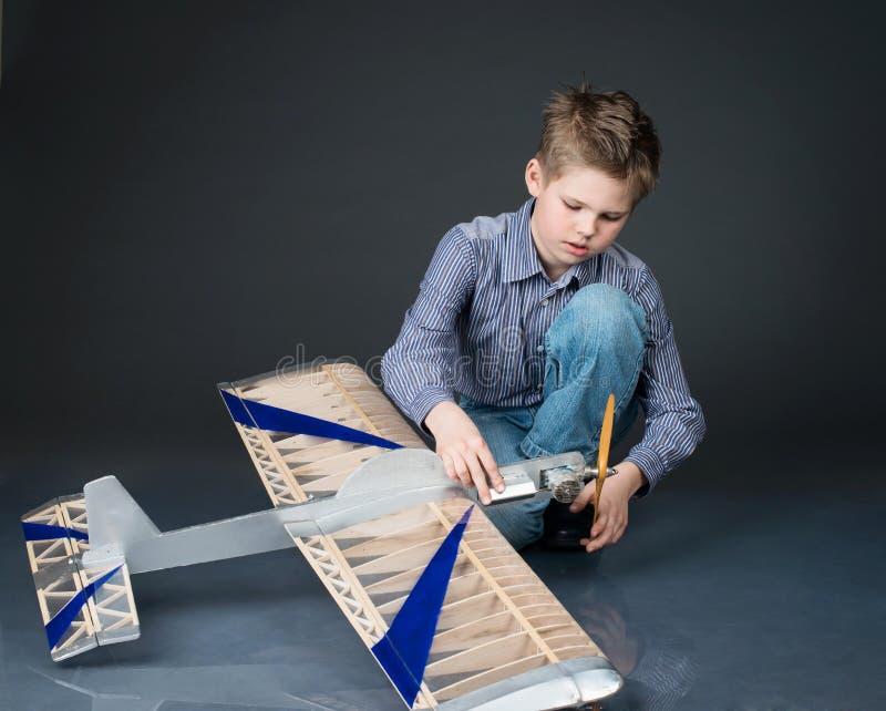 Αγόρι προ-εφήβων που κρατά ένα ξύλινο πρότυπο αεροπλάνων Παιχνίδι παιδιών με πραγματικό στοκ φωτογραφία