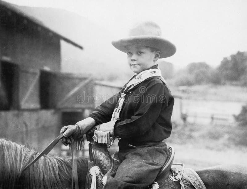 Αγόρι σε ένα καπέλο κάουμποϋ σε ένα άλογο (όλα τα πρόσωπα που απεικονίζονται δεν ζουν περισσότερο και κανένα κτήμα δεν υπάρχει Εξ στοκ εικόνες με δικαίωμα ελεύθερης χρήσης