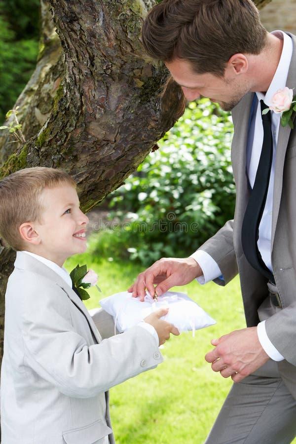 Αγόρι σελίδων που δίνει το γαμήλιο δαχτυλίδι στο νεόνυμφο στοκ φωτογραφίες