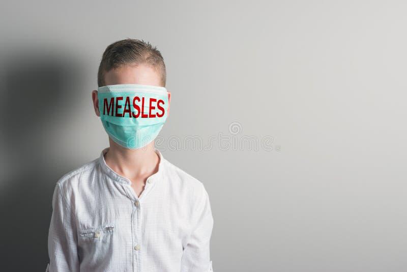 Αγόρι σε μια ιατρική μάσκα με την κόκκινη ΙΛΑΡΑ επιγραφής στο πρόσωπό του στο φωτεινό υπόβαθρο στοκ εικόνα