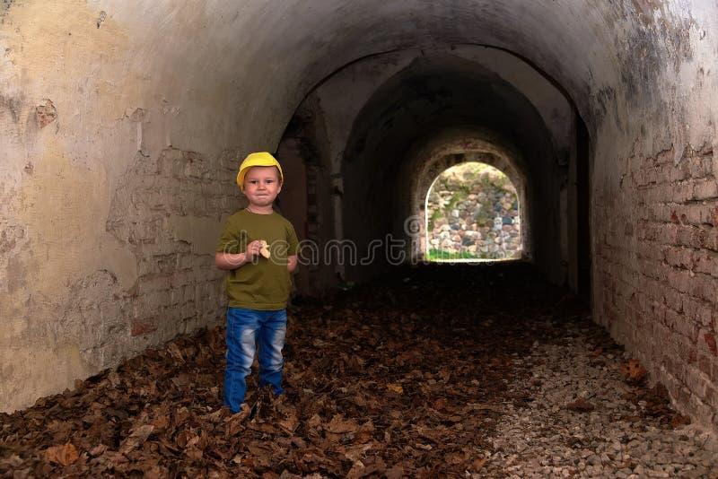 Αγόρι σε μια κίτρινη ΚΑΠ στις καταστροφές στοκ εικόνες