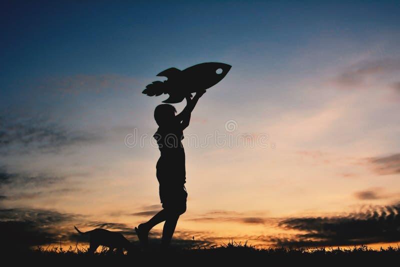 Αγόρι σκιαγραφιών που κρατά ένα έγγραφο πυραύλων και που παίζει με λίγο σκυλί στοκ εικόνα