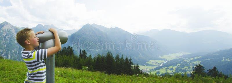 Αγόρι στα βουνά που κοιτάζει μέσω να φανεί γυαλί στοκ φωτογραφία