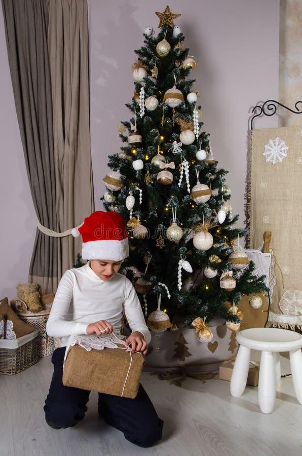 Αγόρι στα κόκκινα δώρα Χριστουγέννων ανοίγματος καπέλων Santa στοκ φωτογραφίες