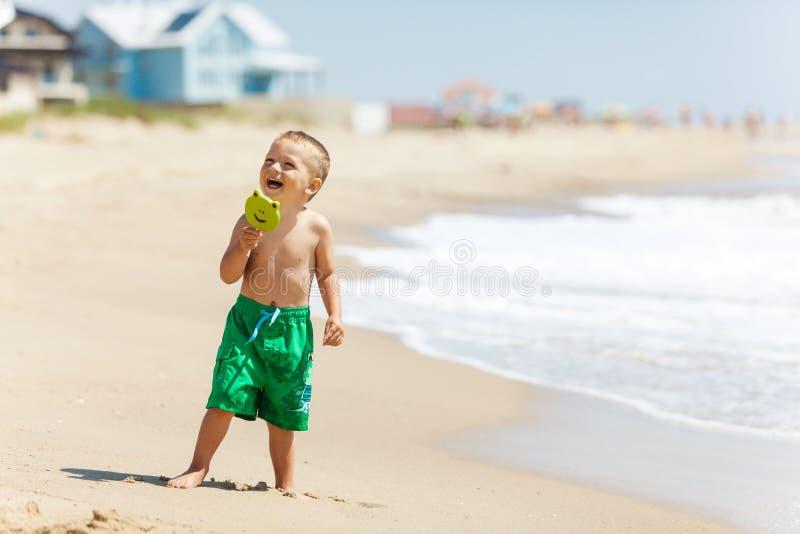 Αγόρι στην παραλία με την καραμέλα στοκ φωτογραφία