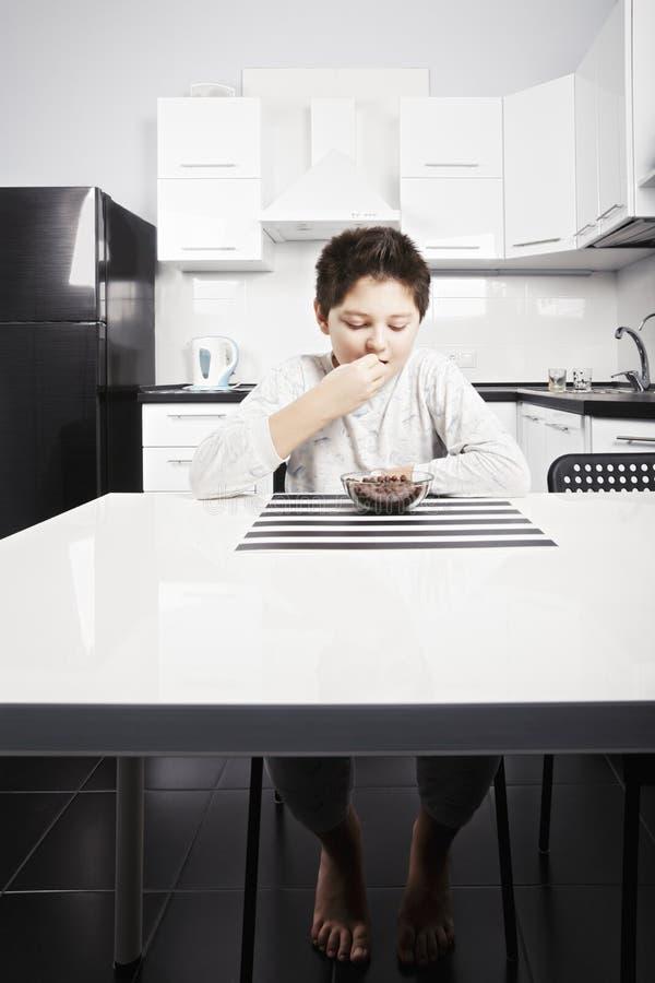 Αγόρι στην πυτζάμα που τρώει τα δαγκώματα δημητριακών στοκ φωτογραφία με δικαίωμα ελεύθερης χρήσης