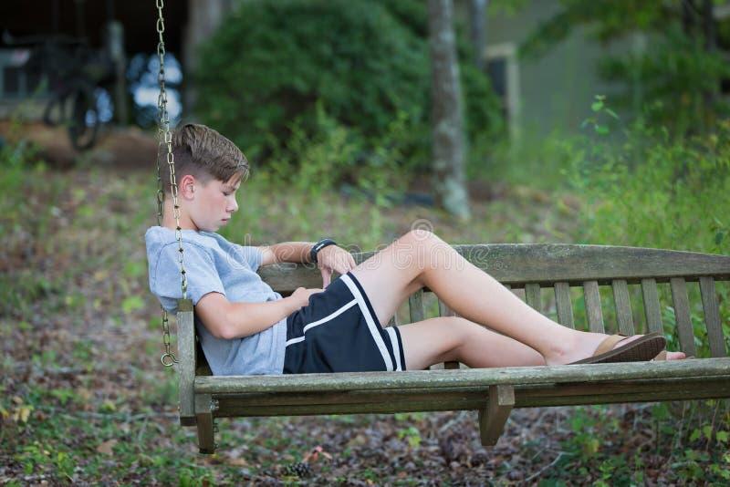 Αγόρι στην ταλάντευση που παίζει ή που στο τηλέφωνο στοκ εικόνα