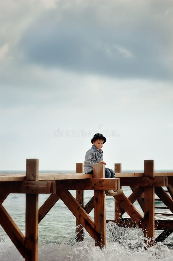 Αγόρι στη γέφυρα στη θάλασσα στοκ εικόνα