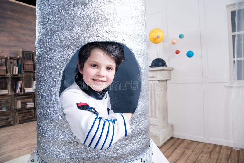 Αγόρι στη συνεδρίαση κοστουμιών αστροναυτών στον πύραυλο παιχνιδιών στοκ εικόνα με δικαίωμα ελεύθερης χρήσης