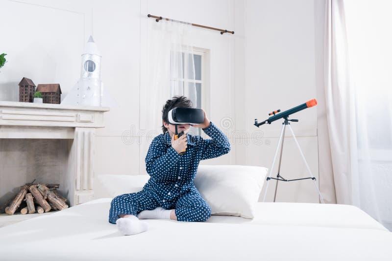 Αγόρι στις πυτζάμες και παιχνίδι κασκών εικονικής πραγματικότητας με walkie-talkie στοκ εικόνες