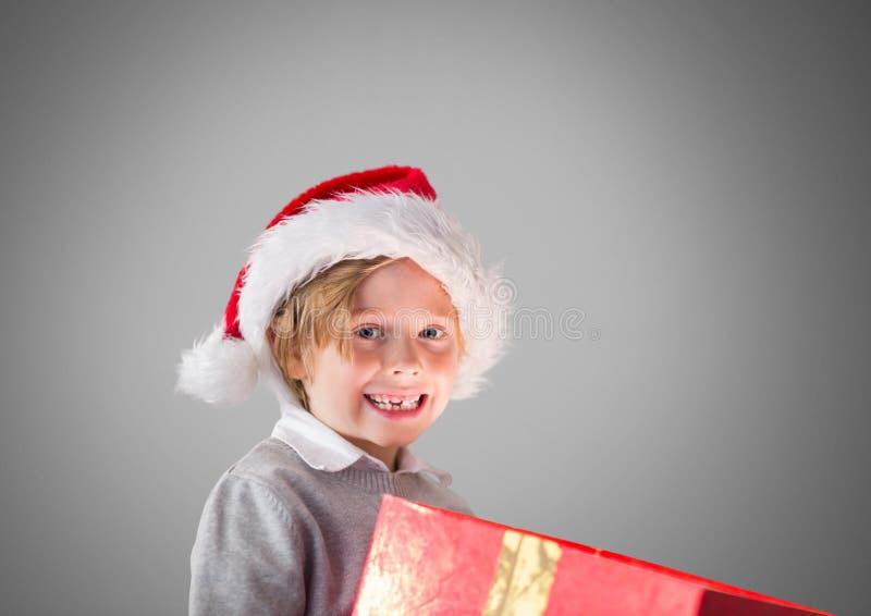 Αγόρι στο γκρίζο κλίμα με το δώρο και το καπέλο Χριστουγέννων Santa απεικόνιση αποθεμάτων
