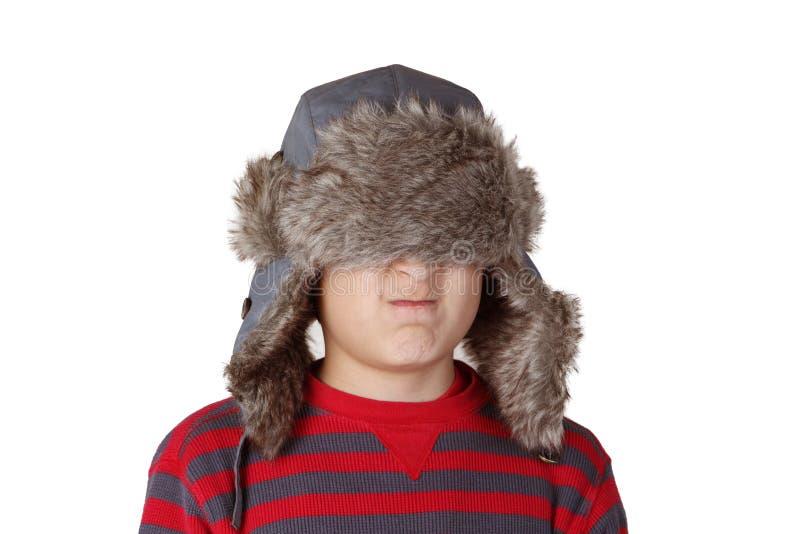 Αγόρι στο γούνινο καπέλο που τραβά τα αστεία πρόσωπα στοκ φωτογραφίες με δικαίωμα ελεύθερης χρήσης