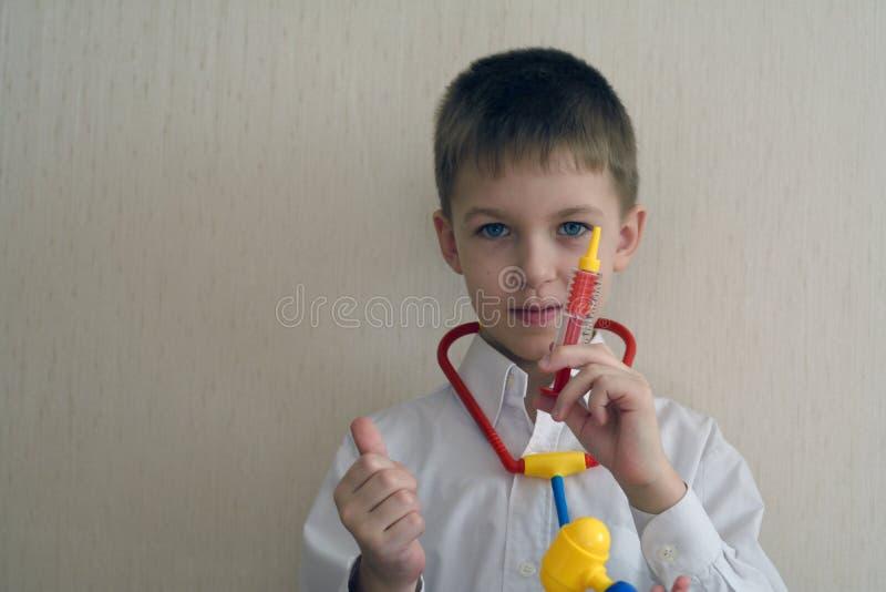 Αγόρι στο λευκό παίζοντας γιατρό παλτών με ένα cyringe στοκ εικόνες με δικαίωμα ελεύθερης χρήσης