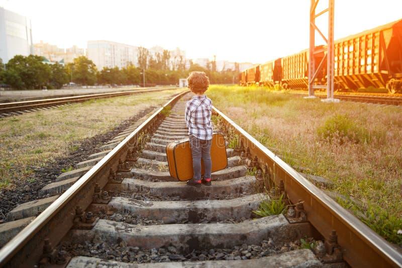 Αγόρι στο ελεγμένο πουκάμισο που στέκεται στους σιδηροδρόμους στοκ φωτογραφίες