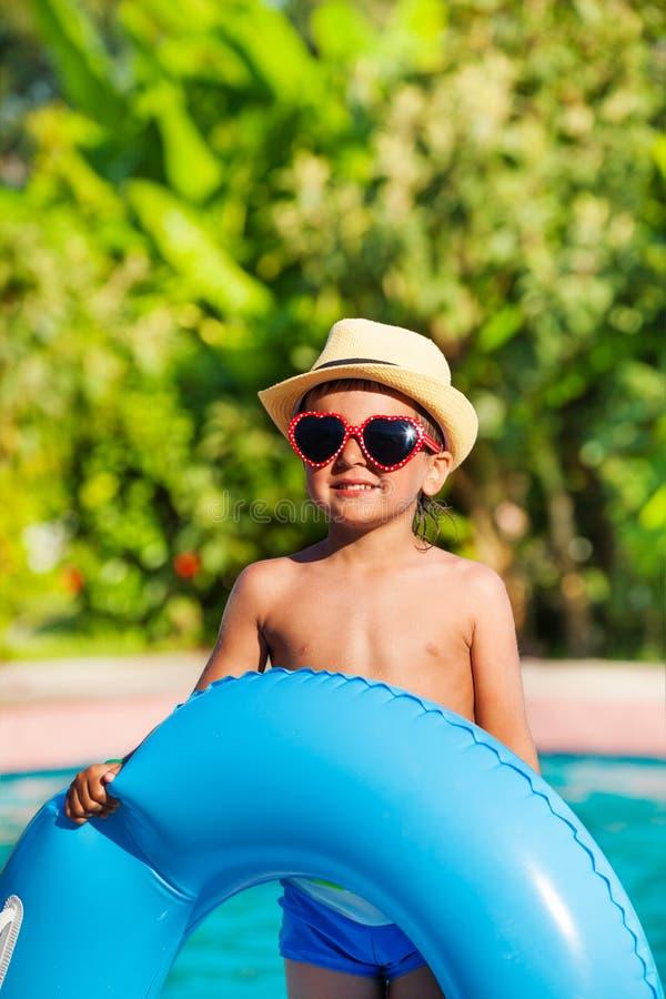 Αγόρι στο καπέλο και γυαλιά ηλίου που κρατούν το διογκώσιμο δαχτυλίδι στοκ εικόνα με δικαίωμα ελεύθερης χρήσης