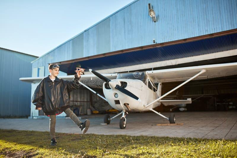 Αγόρι στο μεγάλο πειραματικό σακάκι, που παίζει με το πρότυπο αεροπλάνο κοντά στο υπόστεγο αεροσκαφών στοκ φωτογραφία με δικαίωμα ελεύθερης χρήσης