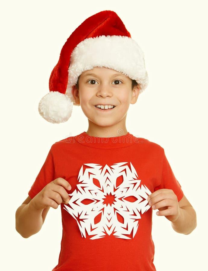 Αγόρι στο πορτρέτο καπέλων santa με μεγάλο snowflake στο λευκό - έννοια Χριστουγέννων χειμερινών διακοπών, κίτρινος που τονίζεται στοκ εικόνες